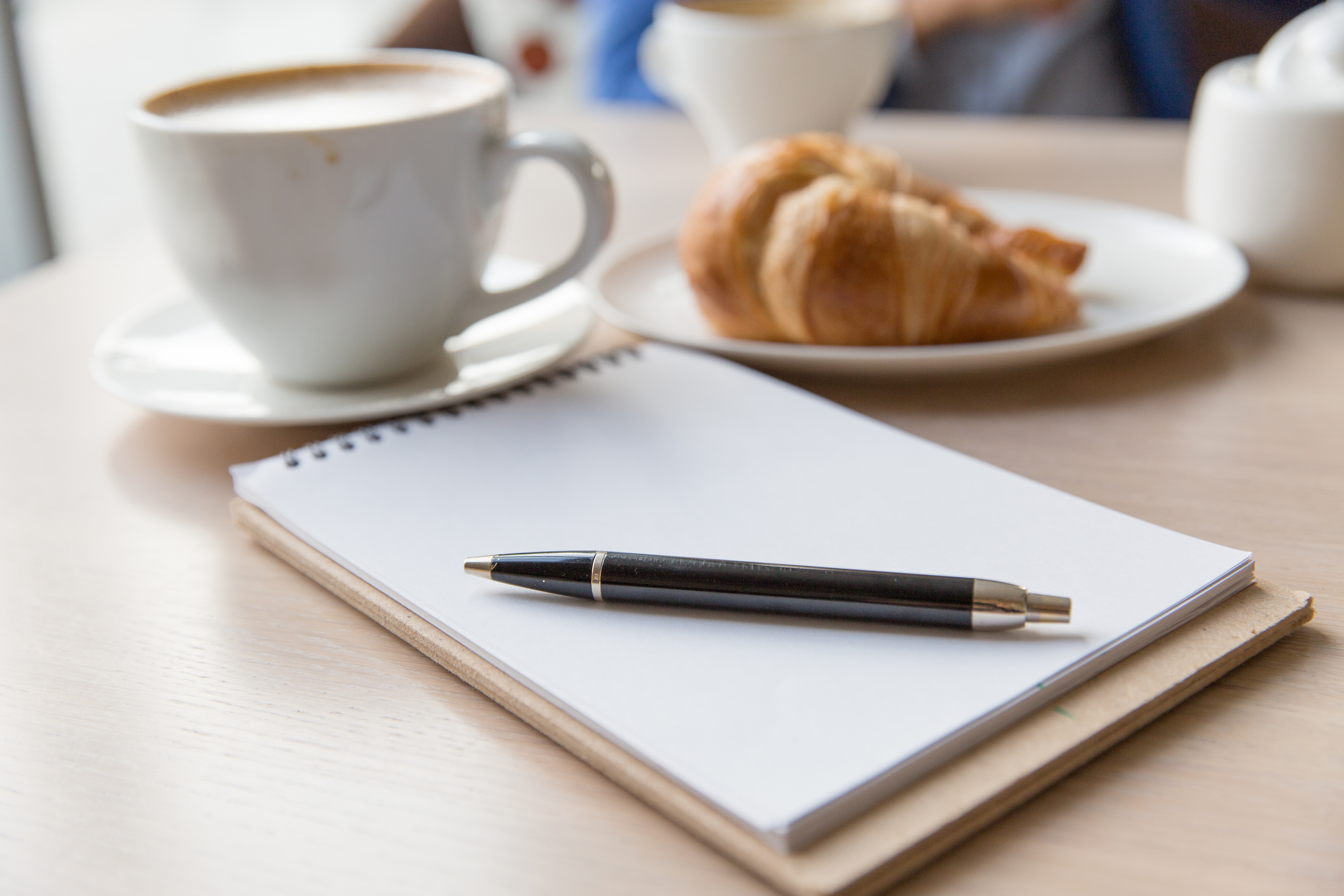 coffee , notebook and  croissant on a wooden table